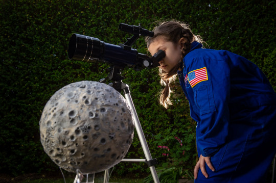 **EMBARGOED UNTIL 14:00HRS GMT / MAY 10, 2021** Elizabeth Norman aka 'Astro Liz' at her home in Leicester. This seven-year-old astronaut in training will become the first child in the world to send something to the moon after impressing the world's leading space pioneers from her back garden. See SWNS story SWSYmoon. Elizabeth Norman is obsessed with space and staged the launch of a massive home-made Vulcan Centaur rocket from her garden earlier this year. Her limitless knowledge and enormous enthusiasm for all things lunar captured the attention of US experts currently prepping the real Vulcan Centaur for the first moon landing in nearly 50 years. United Launch Alliance (ULA) has a miniscule space left on an upcoming mission to send the first ever private pod to land on the lunar surface - which can command a charge of $1,200,000 per kg. But they've offered to take something belonging to 'Astro Liz' - and now a sticker carrying the name of her space blog will be part of the first ever lunar 'time capsule'. Her family from Leicester have even been invited to wave it goodbye on launch day in Florida, USA, at the end of 2021.