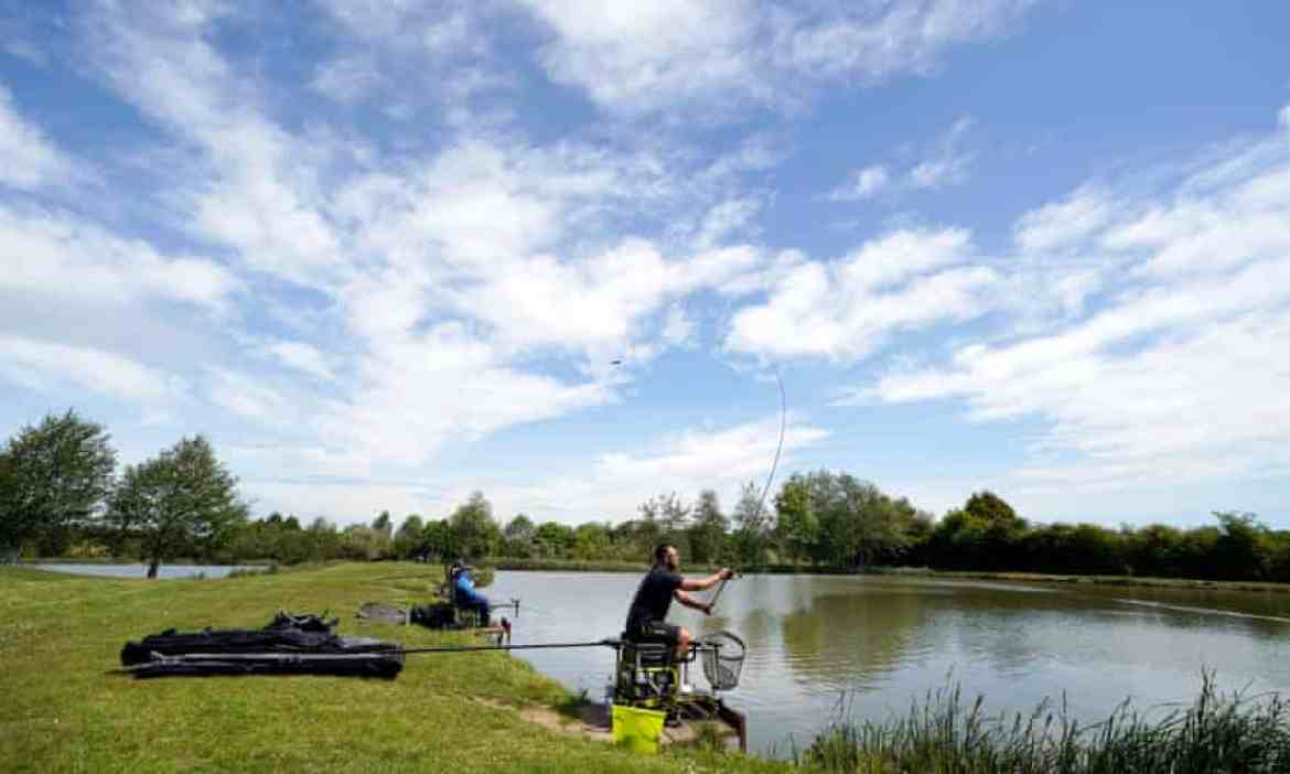 fishing by a lake under a bright blue sky
