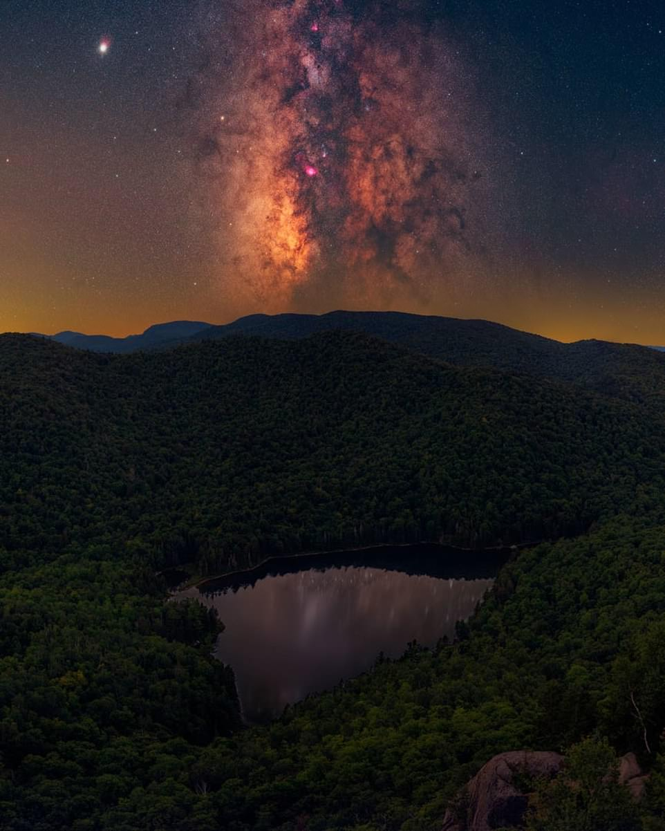 """'ADK Magic'— by Daniel Stein in the Adirondack Mountains, New York. Mr Stein said: 'Tucked away in upstate NY, the Adirondacks region consists of six million acres of land designated as """"Forever Wild"""". It is home to some of the last known darkest skies on the East Coast. I feel like I am home when I am hiking in the Adirondacks. This shot, then, captures the magic which I feel fills my heart when I am there. Not only does it consist of a lake which seems to take the formation of a heart itself, but it also shows just how much the East Coast has to offer: beautiful woodlands combined with still water and rolling hills'"""