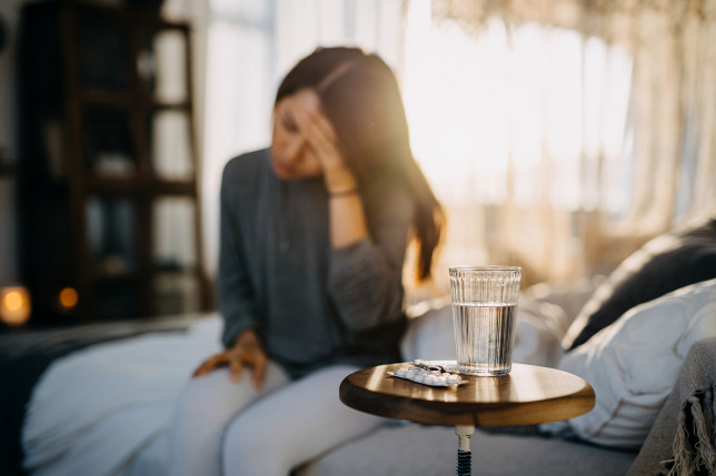 Young Asian woman sitting on the bed feeling sick and suffering from a headache, a glass of water and medicine on the side table