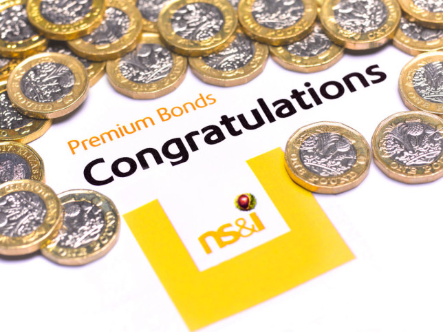 A collection of pound coins surrounding a sign that says cPremium Bonds congratulations.
