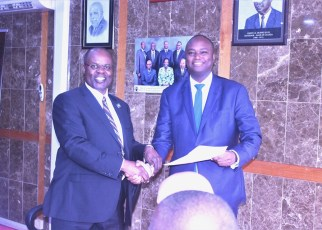 Deputy Governor, Dr. Louis Kasekende (right) hands Stanbic Bank CEO Patrick Mweheire the award