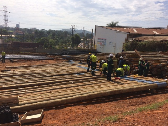 Umeme employees sorting out wooden poles at their yard in Lugogo Kampala. In the near future, the company will stop using wooden poles.