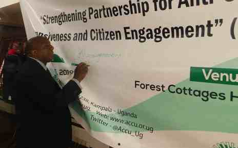 The Deputy Inspector General of Government George Bamugemereire signing on the project banner as sign of commitment to support the project