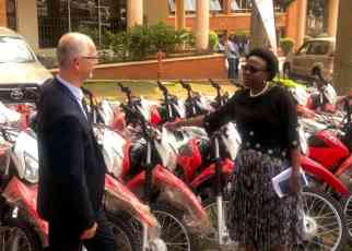 Health Minister Ruth Aceng (Right) receiving the motorcycles and ambulances from UNHCR's Joël Boutroue in Kampala on August 22