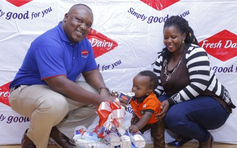 Vincent Omoth Marketing Manager Fresh Dairy (Left) hands over an assortment of Fresh Dairy products to Nellywn Ahirweomugisha (Centre) and his mother (Right).
