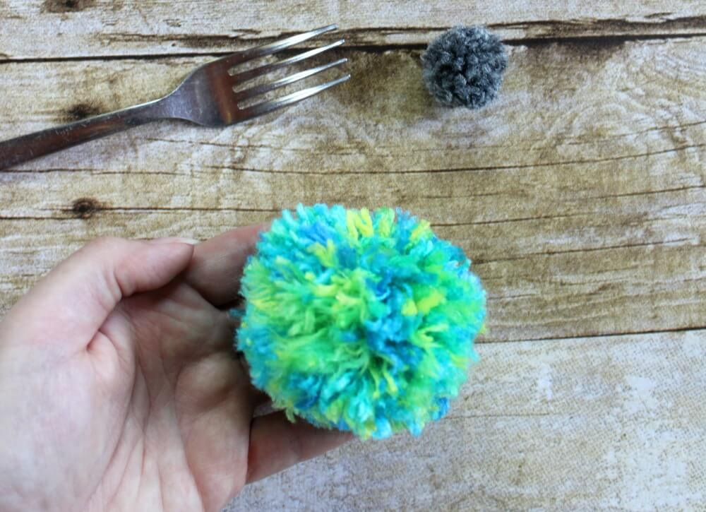 Here are two easy ways to make a DIY yarn pom pom with no special equipment. Make these fluffy pom poms in multiple sizes for your next craft project.