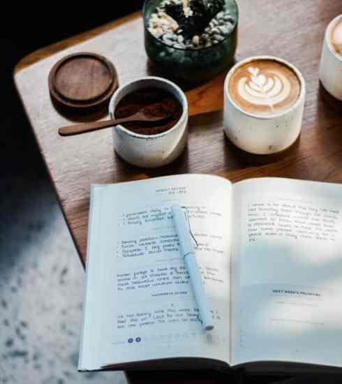 journal and cups of coffee on table