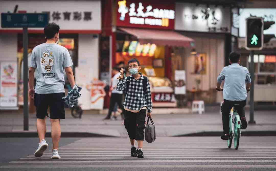 people in masks walking along street