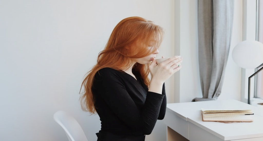 person sipping from a mug at a desk