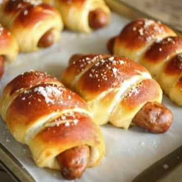 Pretzel Wrapped Brats are bratwurst or sausage wrapped in a fabulous pretzel dough, boiled and then bakedare grilled bratwurst wrapped in a soft pretzel dough. Takes a bit of time to let the dough rise, but so worth it. A grown up version of pigs-in-a-blanket. |butterandbaggage.com