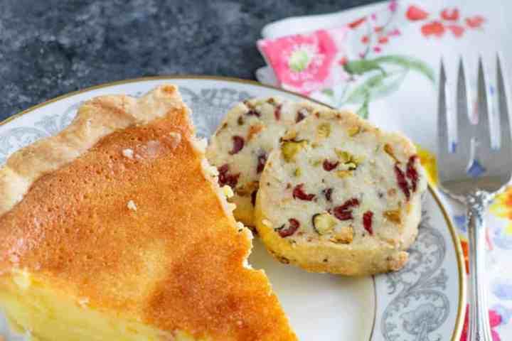A piece of lemon chess pie with a pistachio shortbread cookie