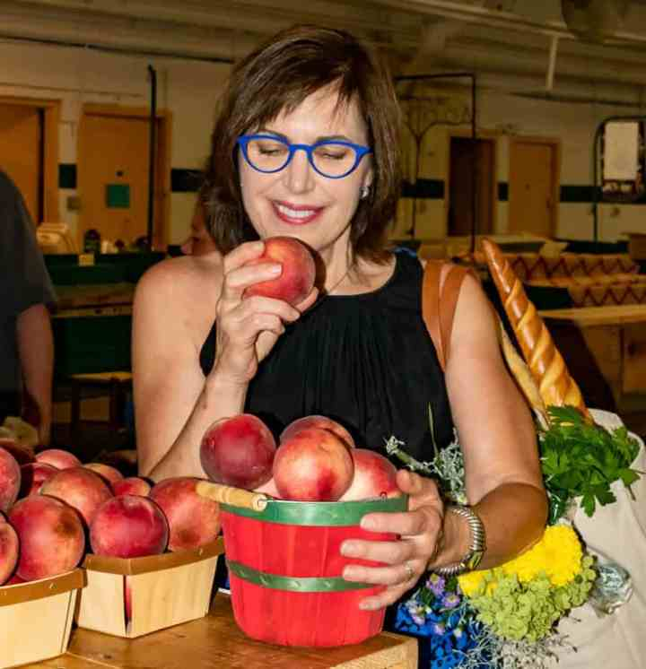 Barbara holding a peach at the farmers market