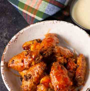 A bowl of baked buffalo chicken wings with a small bowl of blue cheese dipping sauce next to it