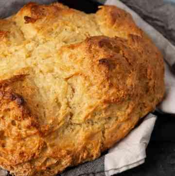 A loaf of Irish soda bread in a cloth napkin