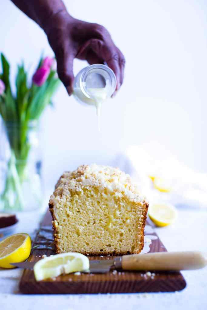 a hand pouring glaze over lemon bread