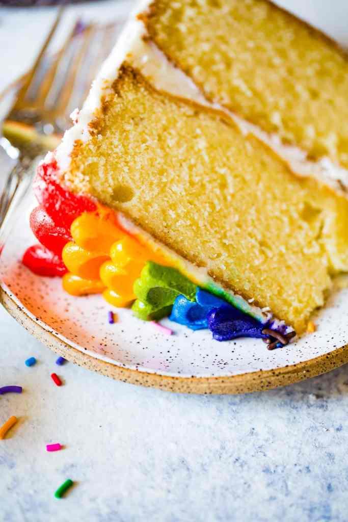 close up shot of a slice of vanilla almond rainbow cake