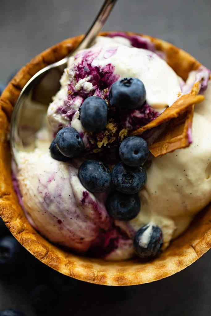 scoops of ice cream in a waffle bowl with blueberries