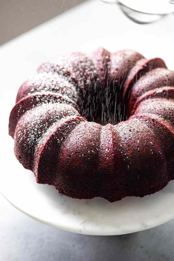 red velvet bundt cake with falling powdered sugar