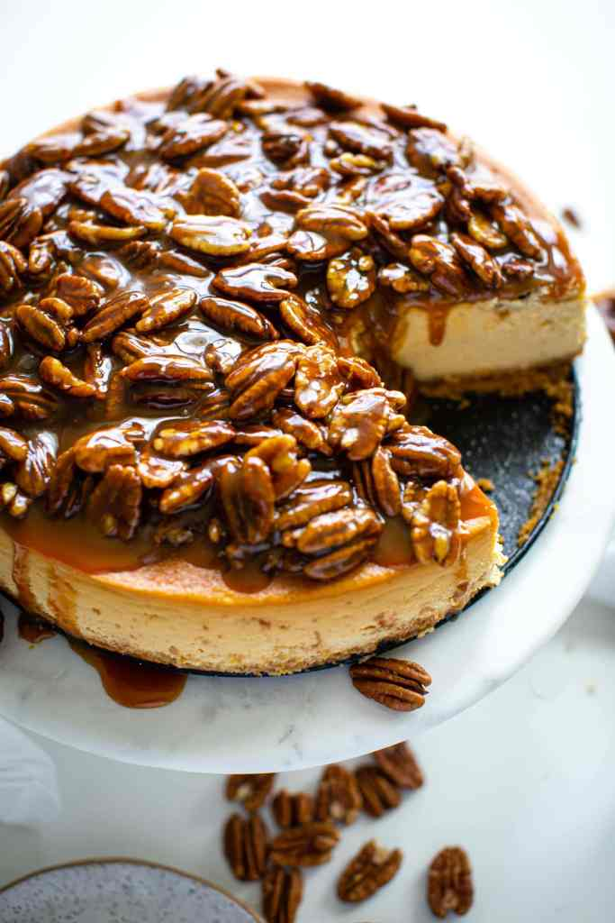 pecans in a caramel sauce sitting on top of cheesecake with pecans on the side