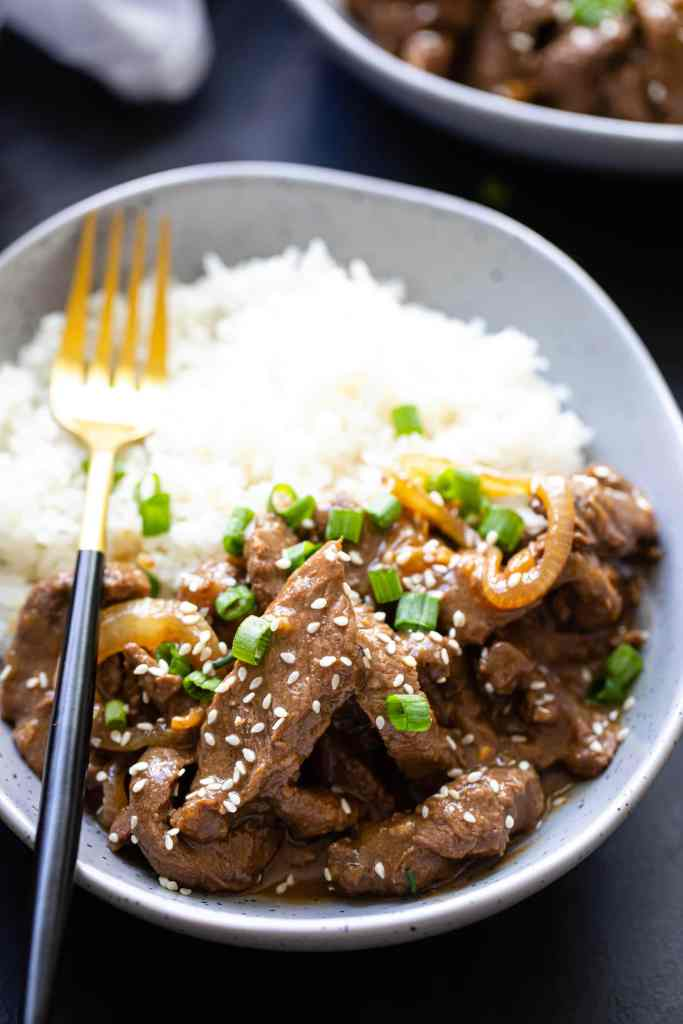 close up shot of beef and rice in gray bowl with gold and black fork