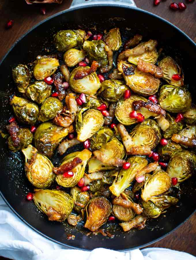 brussels sprouts in a gray skillet on a wooden surface