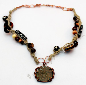 This beautiful antique Spanish Coin is hung from a fancy work band worthy of a pirate! Using hemp cord to string various beads (including wood, bone and ceramic) which might be appreciated by a pirate who wants a beautiful way to wear his or her lucky coin!