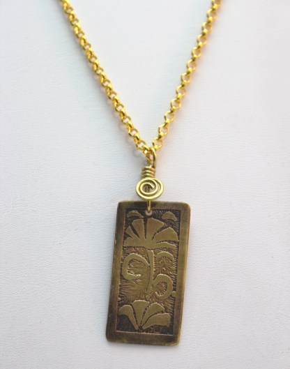 YB Floral Etched Pendant Hanging on White Close-up
