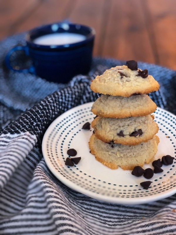 four keto chocolate chip cookies stacked on top of each other with a glass of milk In the background