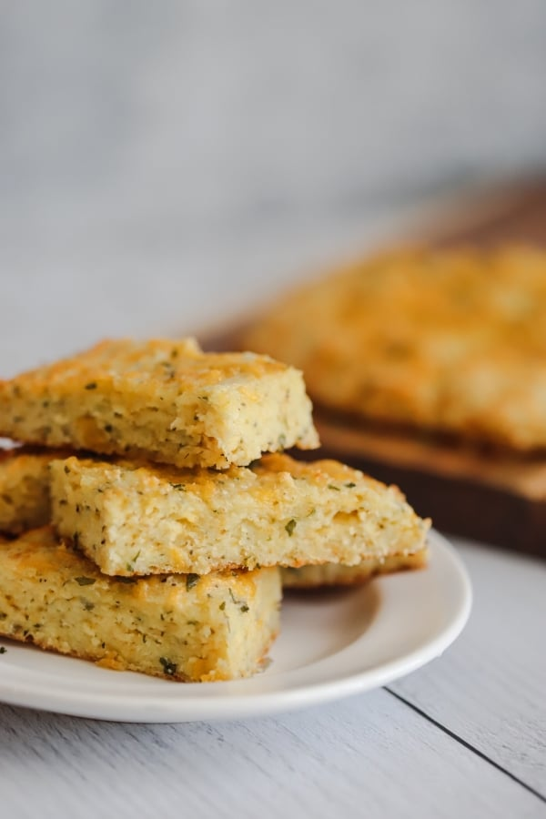 keto garlic bread sticks on a white plate stacked on each other with the rest of the bread sticks laid flat in the background