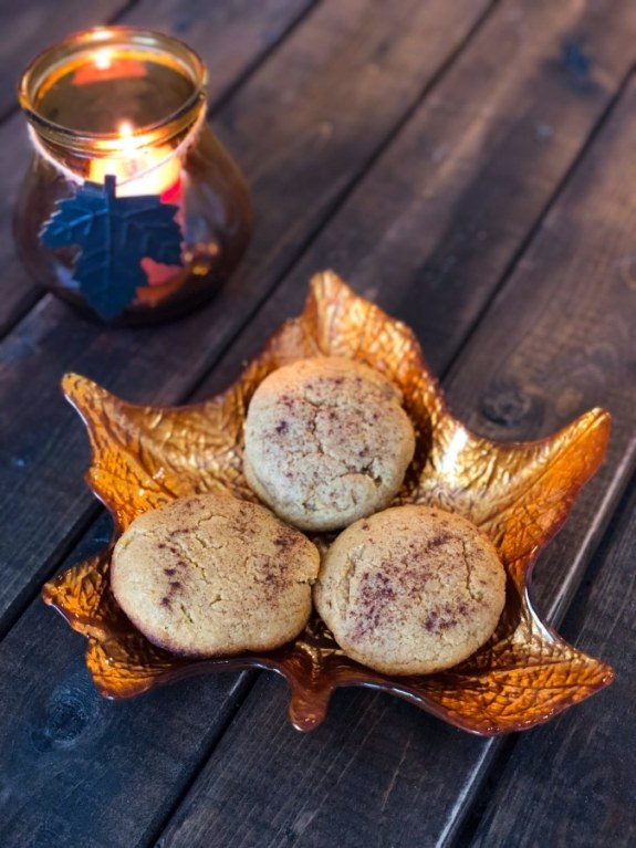 three pumpkin cookies on a fall designed leaf plate next to a pumpkin scented candle