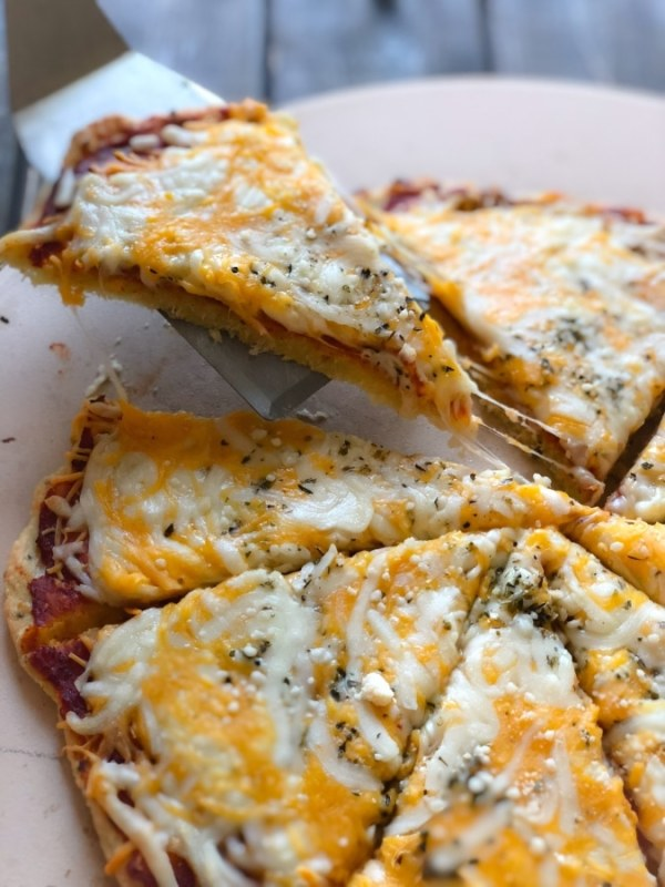 cheesy keto pizza with a slice being lifted off the pizza stone
