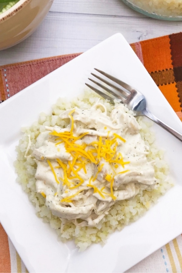 top view of instant pot keto cheesy ranch chicken on top of cauliflower rice on a plate
