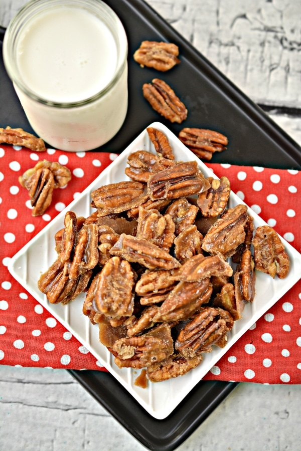 Top view plate of keto candied pecans next to a tall glass of milk