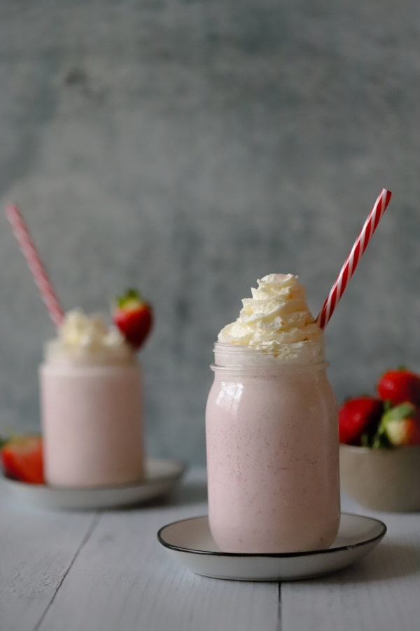 two strawberry cheesecakes shakes with a bowl of strawberries in the background