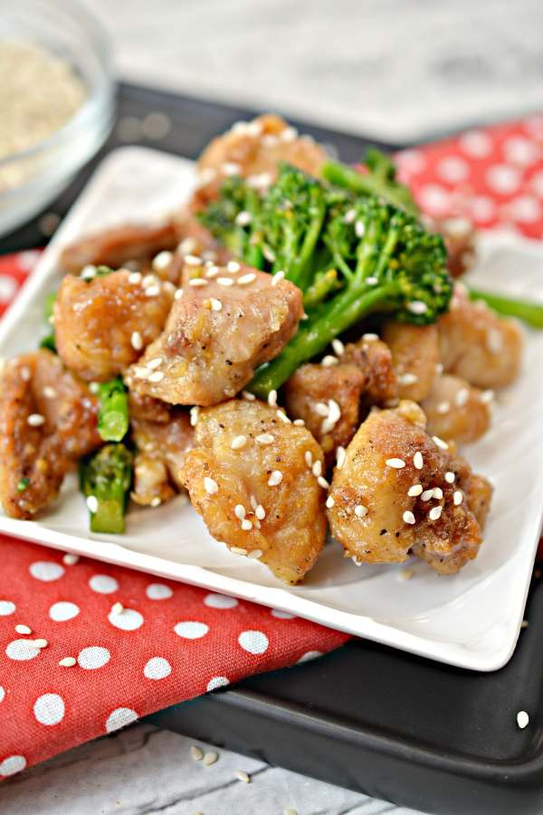 unclose front view of keto sesame chicken on a plate with a few pieces of broccoli