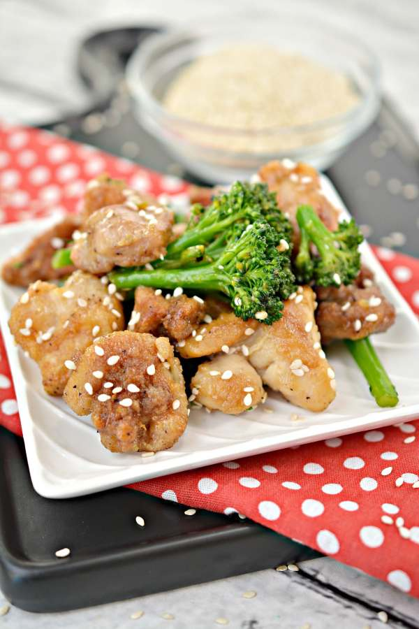 upclose vertical view of keto sesame chicken on a plate with broccoli