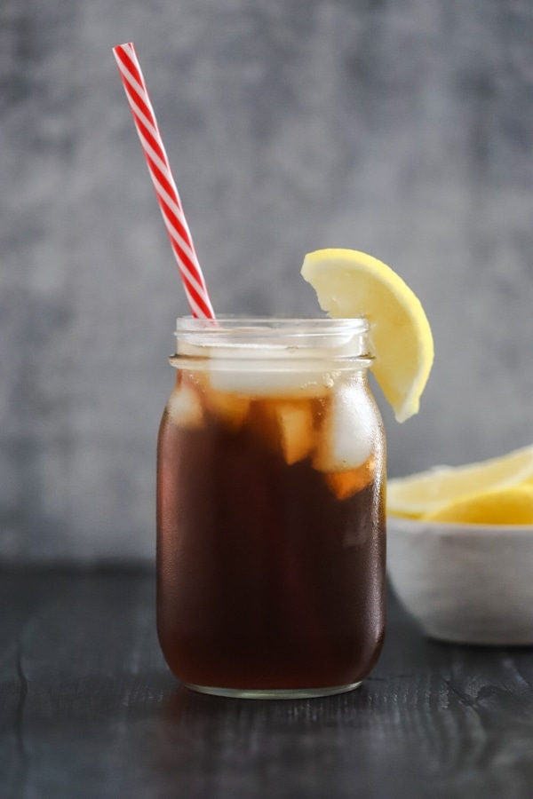 one glass of sweet tea in a mason jar with a bowl of lemons in the background