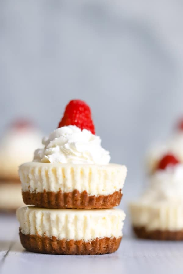two mini cheesecakes on top of each other with a little whip cream and raspberry on top. More mini cheesecakes in the background