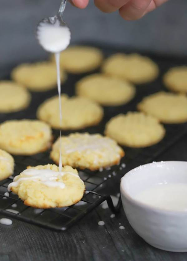 spoonful of glaze hovering over freshly baked lemon cookies being glazed
