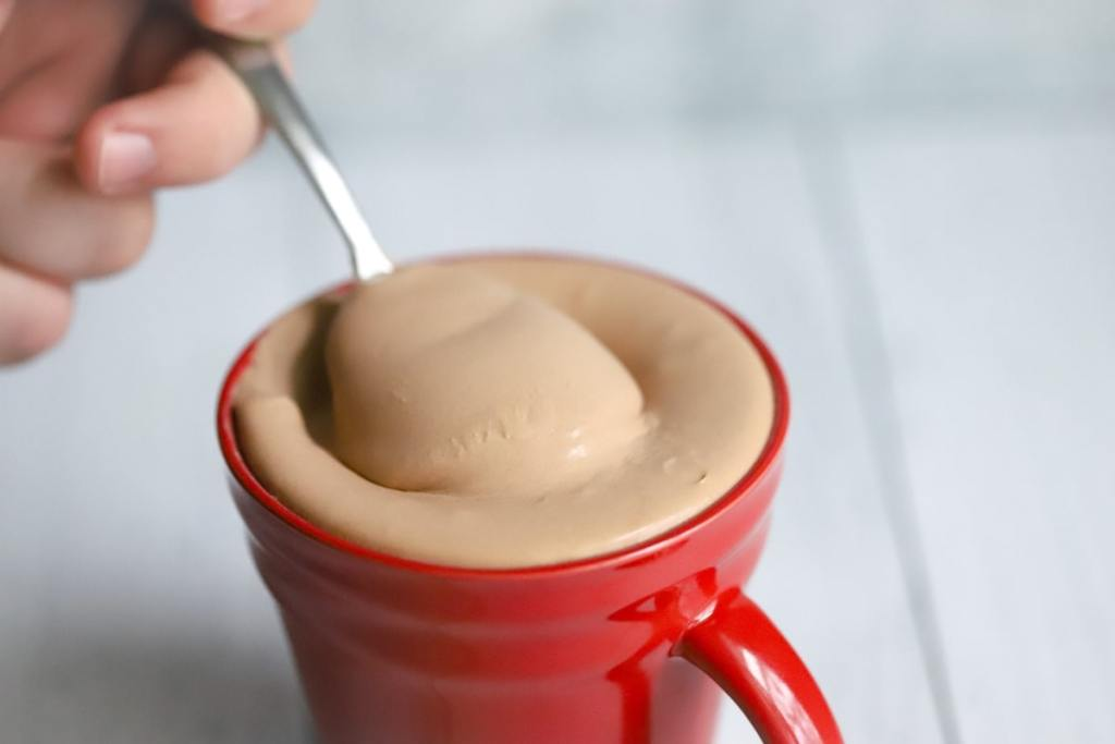 spoonful of keto chocolate frosty being slightly lifted out of the mug
