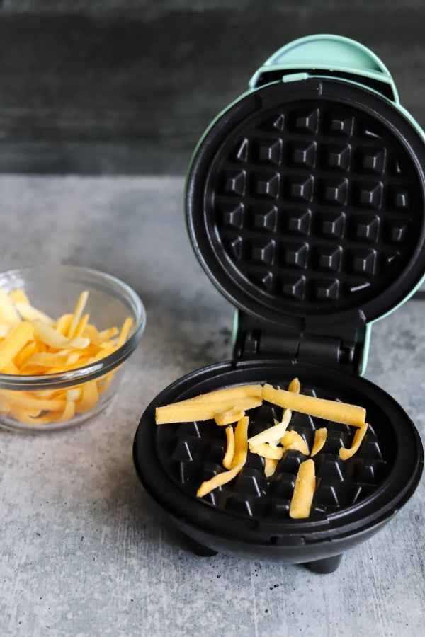 mini waffle maker with some shredded cheese on it and a bowl of shredded cheese on the side