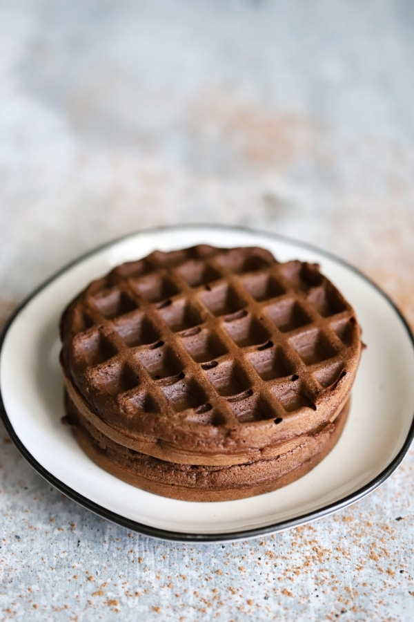 two plain chocolate chaffles with no peanut butter filling sitting centered on a plate