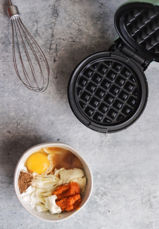 top view photo of pumpkin chaffle ingredients, whisk, and waffle griddle
