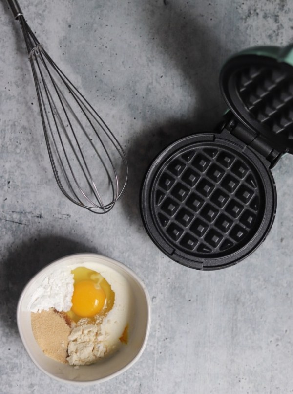 top view of the ingredients in a bowl, a whisk, and the mini waffle griddle