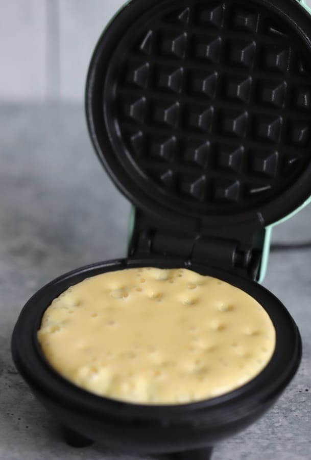 a mini waffle maker with batter in it