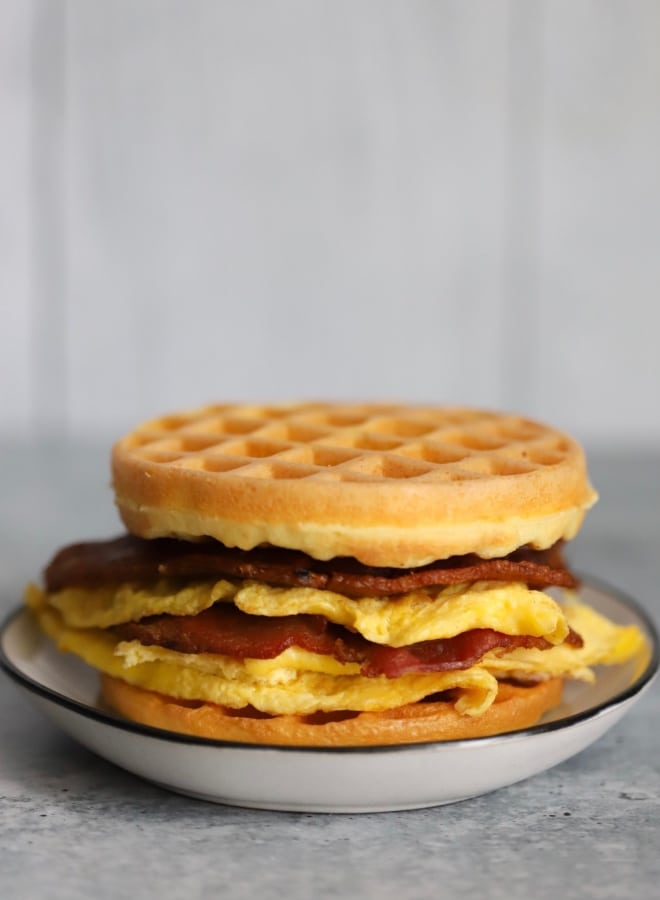 keto chaffle sandwich with bacon and eggs inside in the center on a plate