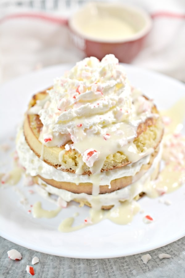 stack of keto peppermint pancakes on a plate with drizzled white chocolate, whipped cream, and crushed peppermint candies on top