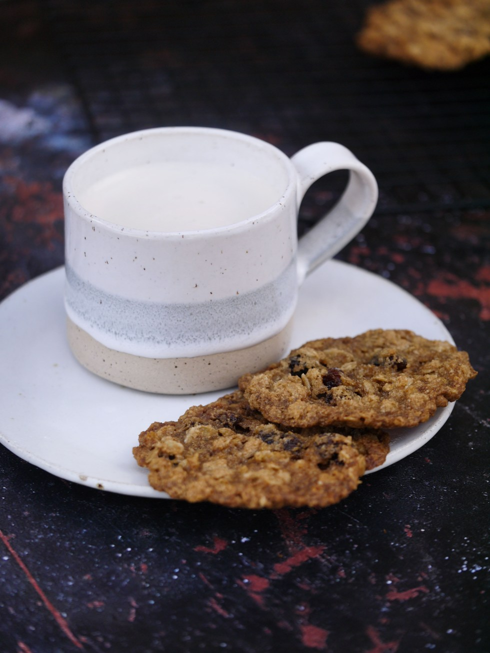 Coffee on saucer with two chewy oatmeal and sultana cookies