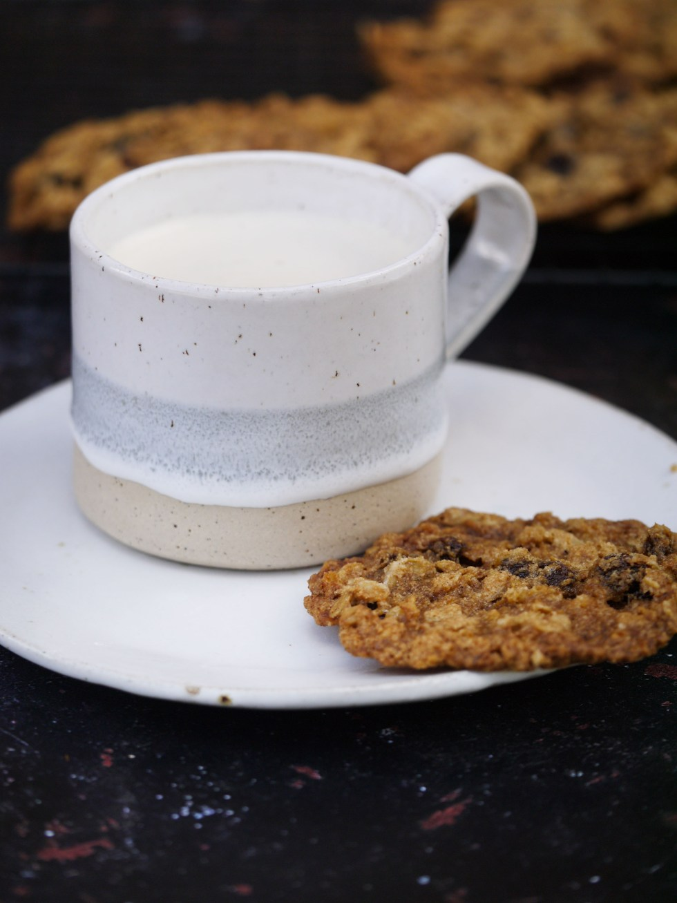 Coffee on saucer with chewy oatmeal and sultana cookie with cookies in background